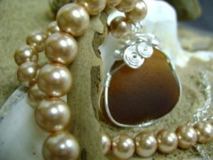 a brown rounded piece of seaglass with pearls